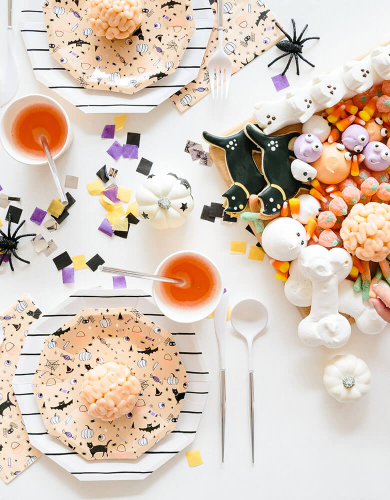 A fun Halloween kids friendly  party table featuring Daydream Society's Hocus Pocus tableware collection and a fun trick or treat themed dessert board with Halloween themed sugar cookies, candy corn, pumpkin gummy, ghost shaped meringue and peeps