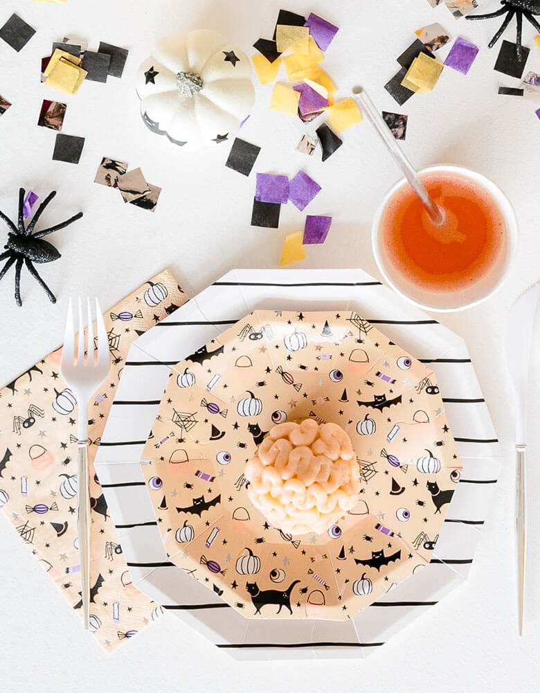 Daydream Society Hocus Pocus Halloween tableware including plates, cups, napkins on a festive Halloween party table with confetti and Halloween spider decorations and Halloween themed treats for kids