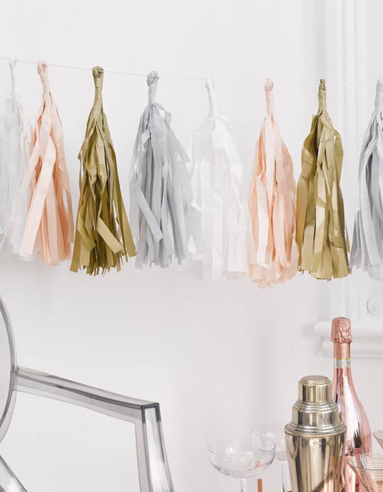 Talking Table Decadent Decs Blush Tassel Garland hung on a wall above a beverage cart