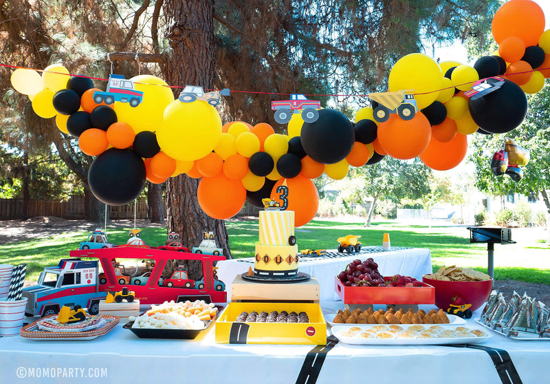 Dig-In Construction Outdoor Party table set up with balloon garland, Truck Garland, Truck Cupcake stand, Cakes and food
