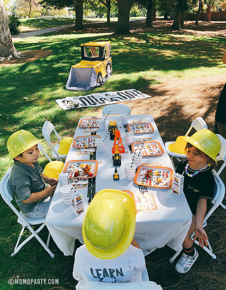 little truck lovers sitting around a outdoor Dig in Construction party table by wearing construction party Hats, eating snacking on Big Rig Large Paper plates with a truck play tent on the grass