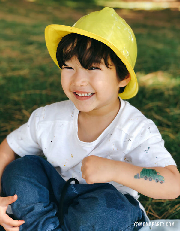A happy young Boy wearing construction party hat and showing his garbage truck temporary tattoo  from Ed Miller designed for Tattly Temporary Tattoos on his arm in a kids Dig in construction birthday Party