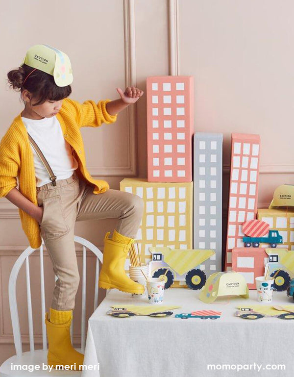 A girl wearing a yellow Construction Party Hat, a yellow sweater, she standing on a chair lifting her yellow rainboot in a Kid Dig In Construction party table. There are Meri Meri Dumper Truck Plates, Construction Party cups and Construction truck napkins, and paper made pastel color building as backdrop. what a Fun modern partware for a kid's construction themed birthday party, Dig in birthday party, big construction vehicle lover, boy's birthday party, kid's birthday party