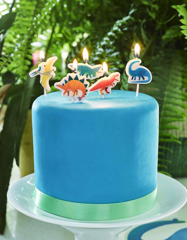 Dinosaur Birthday Candles on top of blue cake