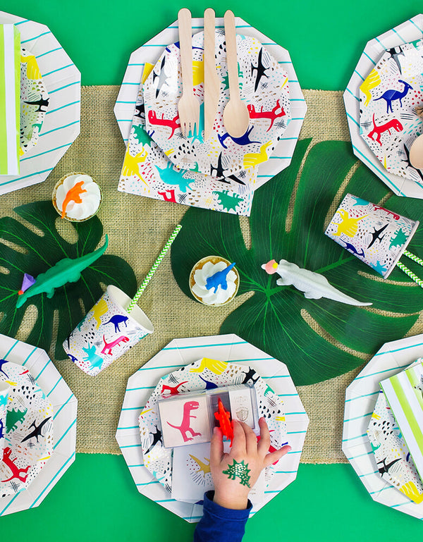 Modern Dinosaur Party Table Set Up with boy's hand