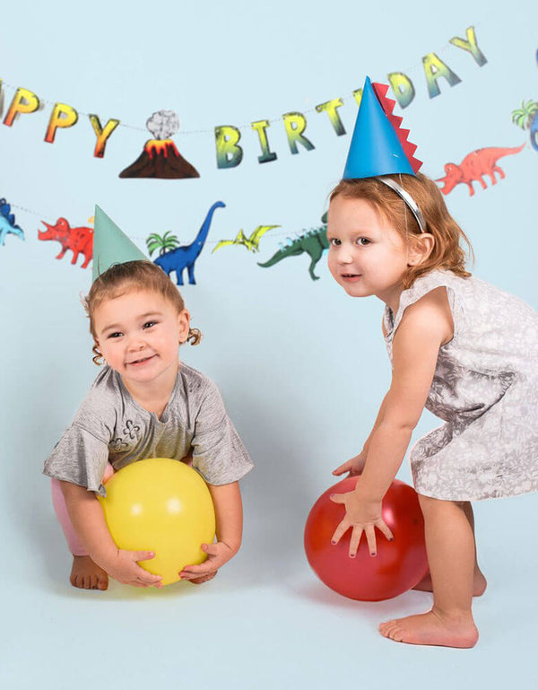 Kids in a dinosaur themed birthday party wearing Merrilulu's Dinosaur Party Hats with spikes in green and blue