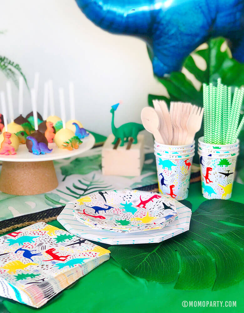 Kids Modern Dinosaur Party Table Set up with Neon Dinosaurs graphic paper plates, napkins, cups, wooden utensil, paper straw, dinosaur cake pop