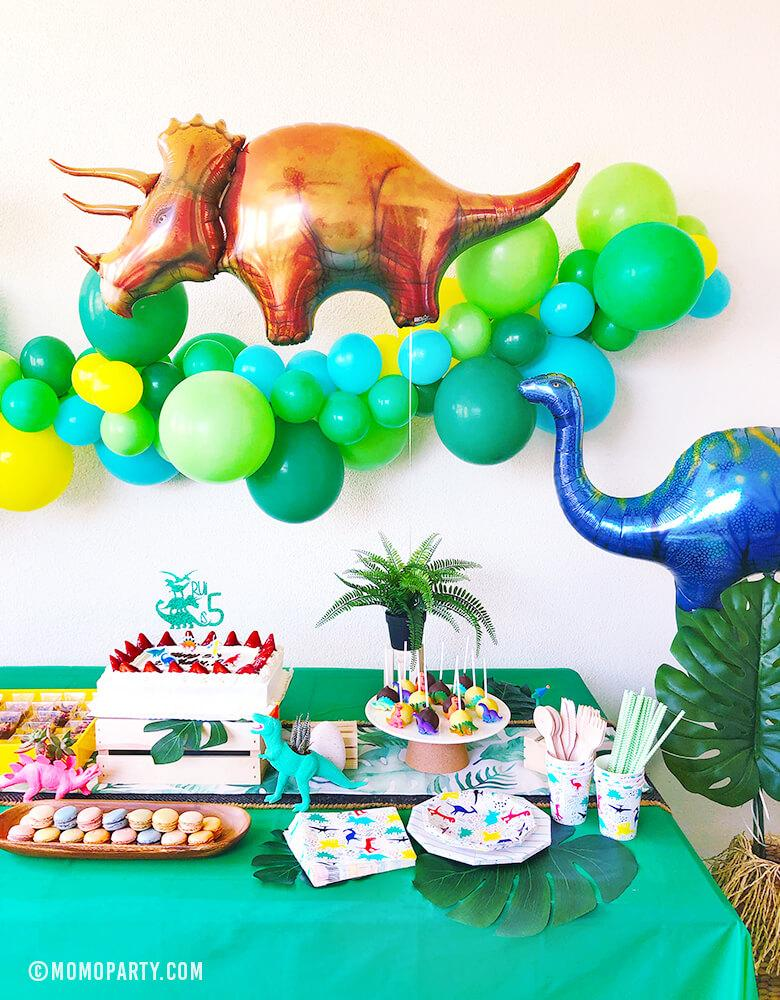 Kids Dinosaur Party Set up with dark green, blue, mint, yellow latex Balloon Garland, Dinosaur foil balloon, neon dino planner, table wears, sweets as table decorations,