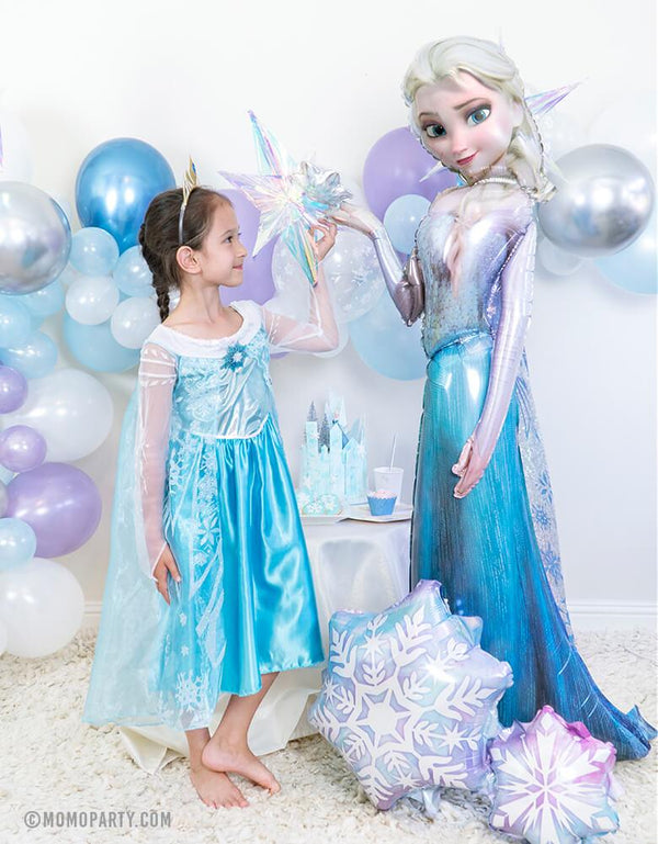 Girl wearing Elsa costume stand next to 57 inch Anagram_Disney Frozen Elsa Airwalker Foil Balloon and Holographic Snowflake Cluster Foil Balloon in a Frozen birthday party