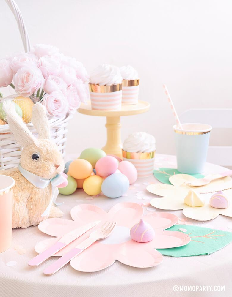 Modern pastel Easter Party dessert table with Pastel Daisy Large Plates, Pastel Cups, Leaf Napkins and Easter Basket and pastel eggs, bunny decoration, and sweets