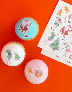 blue, Pink and white cupcakes decorated with Make Bake shop Elving Around Edible Decorating Stickers, include edible stickers with santa, elves, gingerbread man, candy cane Stickers, designed by Hello!Lucky for Make Bake, 100% edible and super kid-friendly. Simply peel it and apply to iced cakes, cupcakes, cookies, These easy baking hacks will be These editable stickers make decorating baked goods so much easier this Holiday season