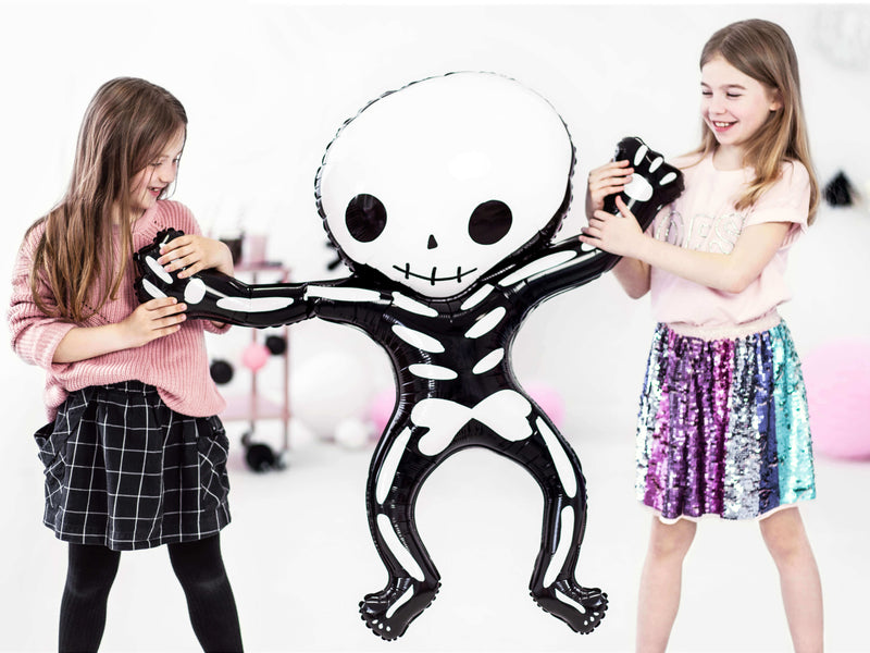 2 Girls holding a Party Deco - Halloween funny Skeleton shape Foil Mylar Balloon in a pink halloween party. This fun skeleton foil balloon like a kid size, also perfect for Kid-Friendly modern spooky halloween party, trick-or-treating halloween party, nightmare before christmas party, witch themed party and all halloween related celebrations
