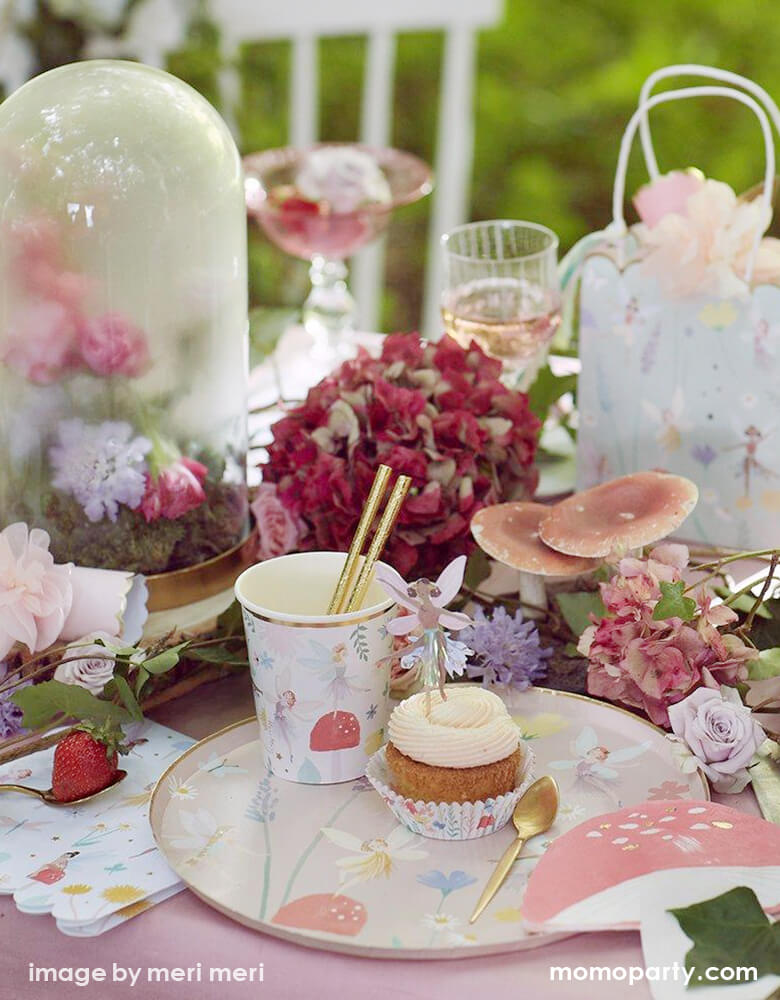 A dreamy outdoor fairy garden party look of a beautiful cream butter cake with Meri Meri Fairy Cake Topper. there are 3 fairies, a toadstool and flowers topper on top of it, a glass of rose, lots of flowers around, cupcake with fairy cupcake topper