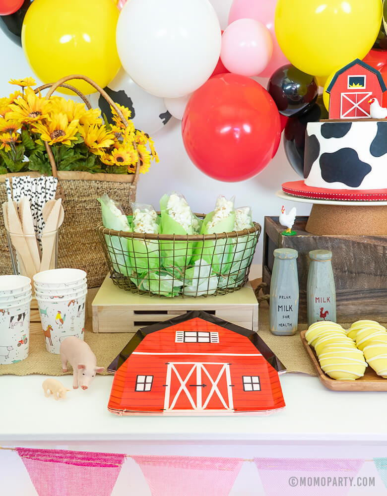 Dessert Table for Barn yard, Farm Animals Birthday Party with Barn house party plate, popcorn corn basket, cow cake, farm animals paper cups, cookies, flowers in the basket, and balloon garland on the back