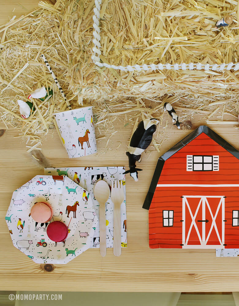 Farm Barnyard Party table inspiration set up with Macarons on the Farm-Animals Small Plates, wooden utensils on top of Farm-Animals Napkins, Cow pattern paper straw inside of Farm animal party Paper Cups, Red Barn house plate, animal toys on the Straw Bale as center piece