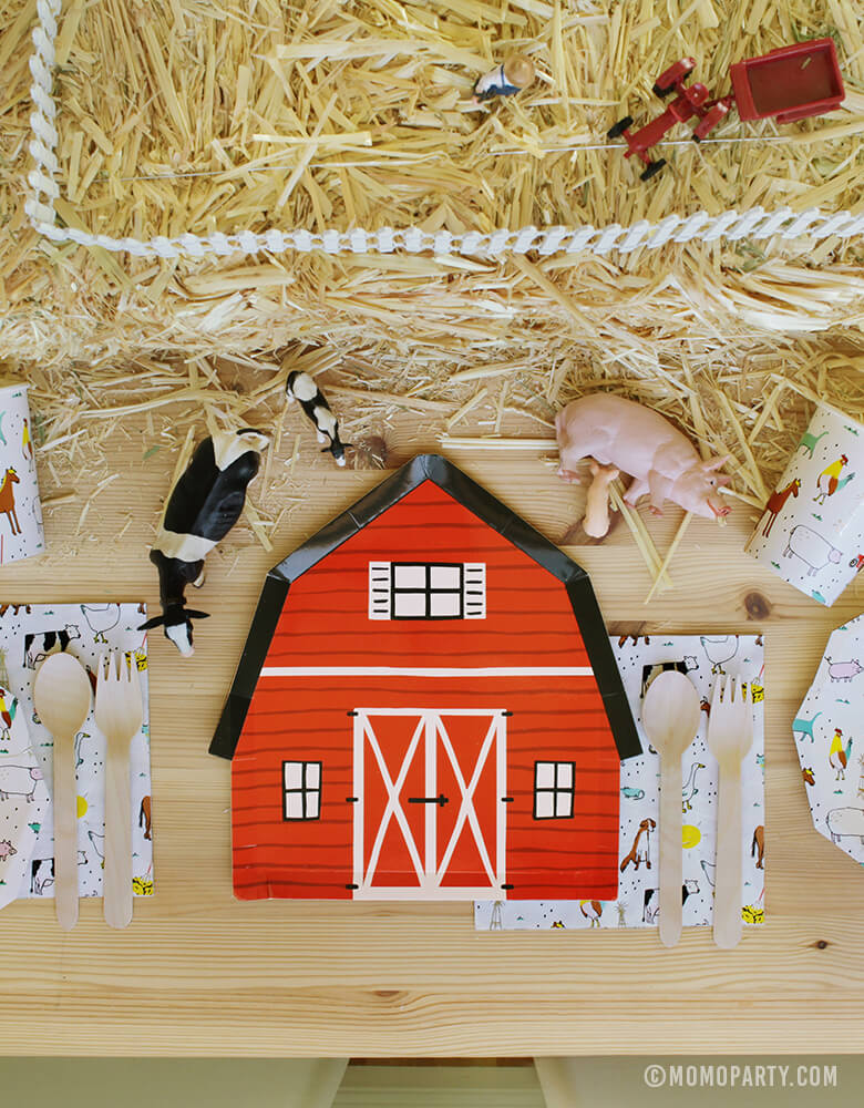 Kids Farm Barnyard Party table set up with Red Barn house plate in the middle, on the Farm-Animals Small Plates, wooden utensils on top of Farm-Animals Napkins, Paper Cups, animal toys on the Straw Bale as center piece