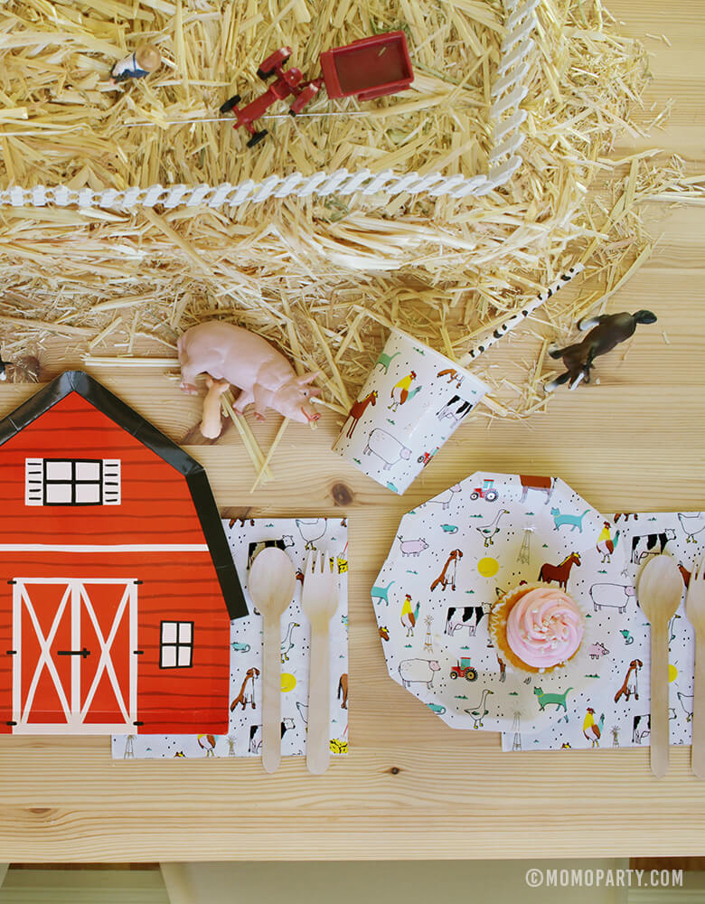 Kids Farm Barnyard Party table set up with cupcake on the Farm-Animals Small Plates, wooden utensils on top of Farm-Animals Napkins, Paper Cups, Red Barn house plate, animal toys on the Straw Bale as center piece