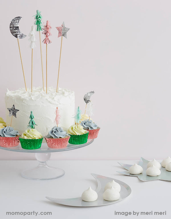 A cake with whipped cream and Festive Tree cake toppers, surrounded by a Set of cupcakes topped with Meri Meri Festive-Tree-Cupcake-Kit featuring Christmas tree, moon and star toppers in pink silver and mint foil