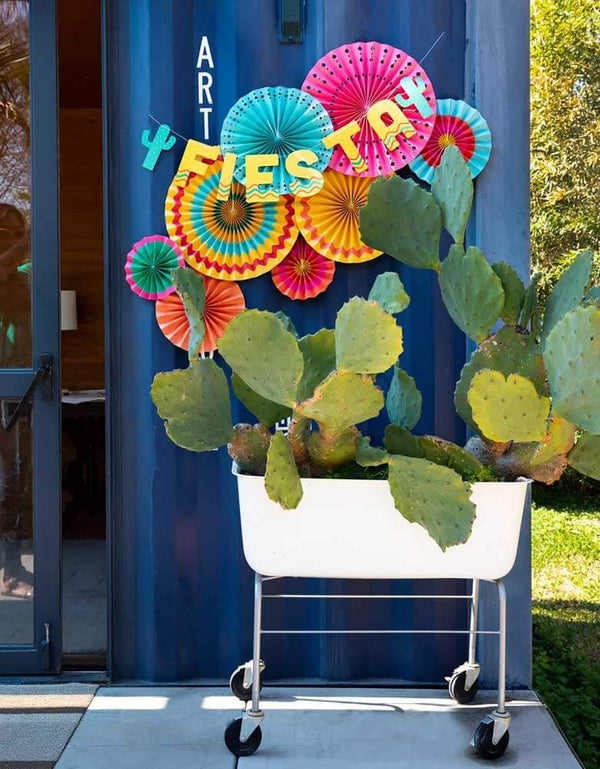 My Minds Eye Fiesta Banner and Fiesta Paper Fans decorations hung across a huge cactus platter for a Fiesta themed party
