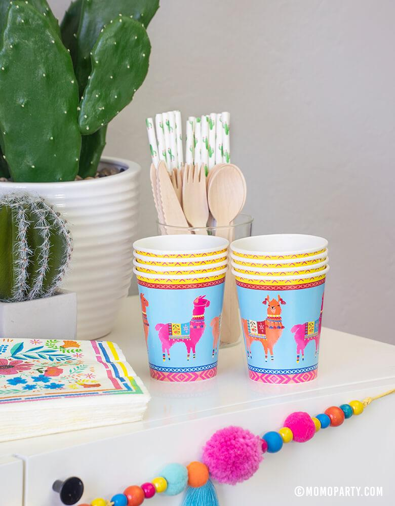 A conner of a party dessert table with Talking Tables Boho Fiesta Llama Cups, Hyper Tropical Wooden Cutlery Set, Cactus printed paper straws, Boho Fiesta Floral Napkins and Boho Fiesta Pom Pom Garland for A Boho Fiesta Themed Party, or Modern Cinco De Mayo Party