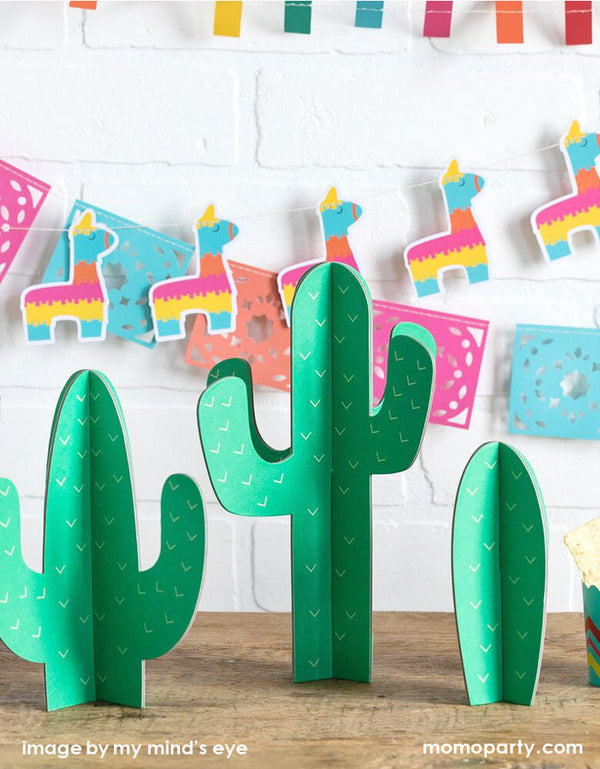 Fiesta celebration dessert table decorated with My-Minds-Eye Fiesta Cactus Tabletop Decor as centerpiece, My-Minds-Eye Mini-Banner-Set with ticker tape banner, llama banner, and papel picados banner as backdrop. These modern and Easy set up party ware are perfect for your next Taco Tuesday gathering, Fiesta birthday party, boho fiesta baby shower, cinco de mayo celebration