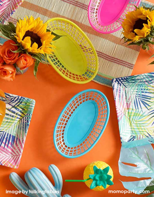 Fiesta themed party table decorated colorful Cuban-inspired food baskets in bright yellow, pink and blue color, pineapple sipper, sunflowers, cactus ceramic, table cloth and tablewares