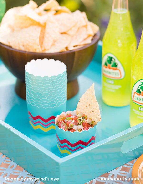 Fiesta party table with a bowl of chips, Jarritos Soda, chips and salsa in the My mind's eye Fiesta Food Cups in a mint blue tray for a fun summer party