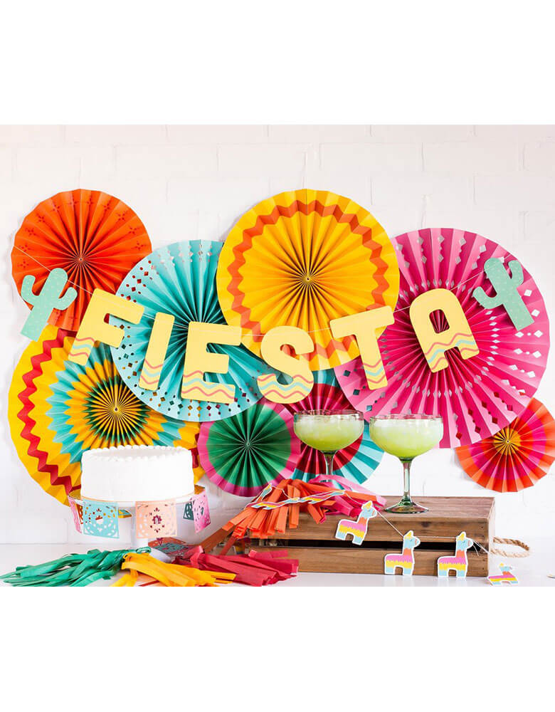 My Minds Eye Fiesta Paper Fans with Fiesta banner and cactus mini banner decorations hung over a fiesta themed party table