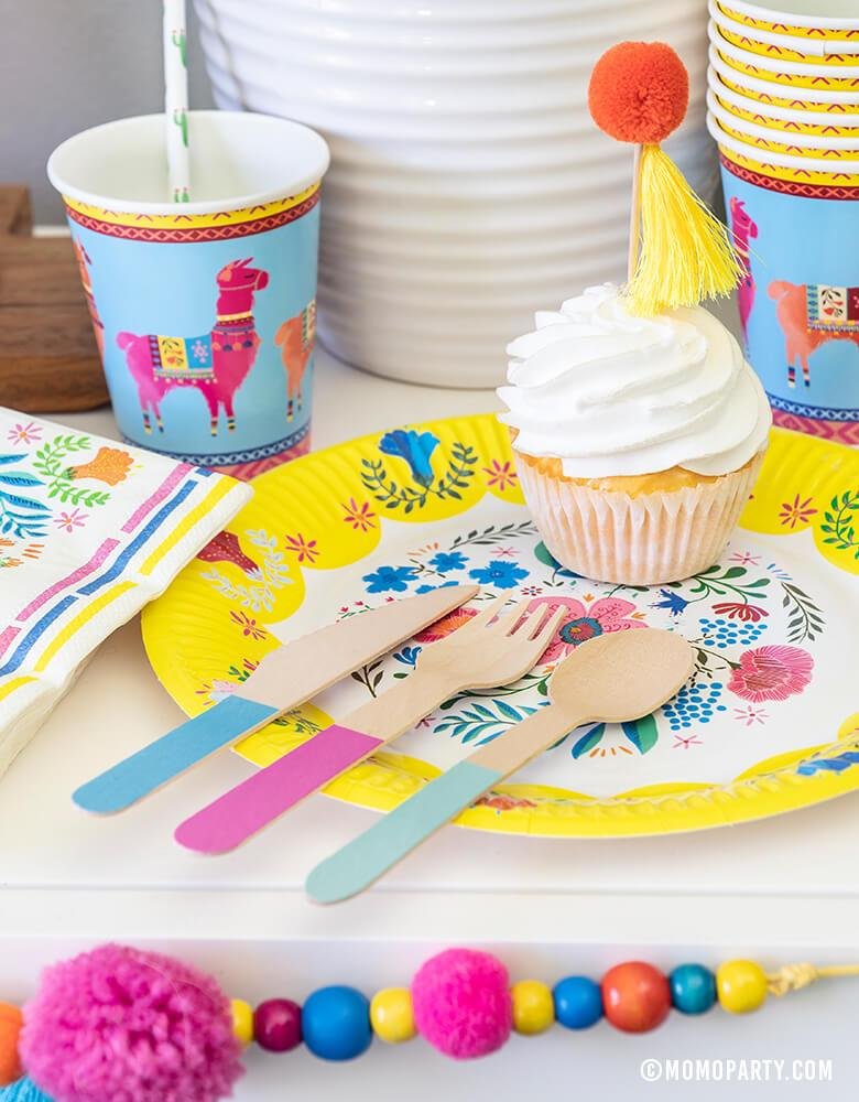 "Desert table with Talking Tables 9"" Boho Fiesta Floral Plate, Boho Fiesta Llama Cups, Hyper Tropical Wooden Cutlery Set, Boho Fiesta Floral Napkins and Boho Fiesta Pom Pom Garland, for A Boho Fiesta Themed Party, Modern Cinco De Mayo Party"