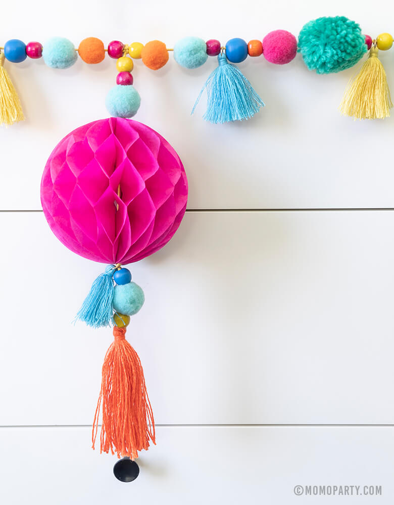 close up look of Talking Table_Boho Fiesta Pom Pom Garland with Pom poms and tassels combined with bead and paper honeycomb details for Fiesta party or cinco de Mayo celebrations or home decoration