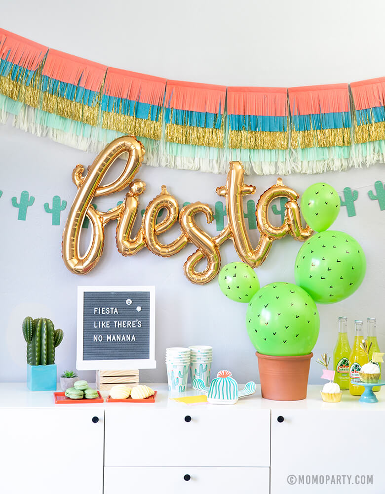 Fiesta Cactus Theme party set up with Meri Meri Colorful Fringe Large Garland, Fiesta Gold Script Mylar Balloon, My Mind's Eye's Cactus Banner as backdrop decoration, Cactus die-cut plates, Cactus paper cups, Diy Cactus Latex balloon in a planter, Macaron and cookies, cupcakes on the dessert table