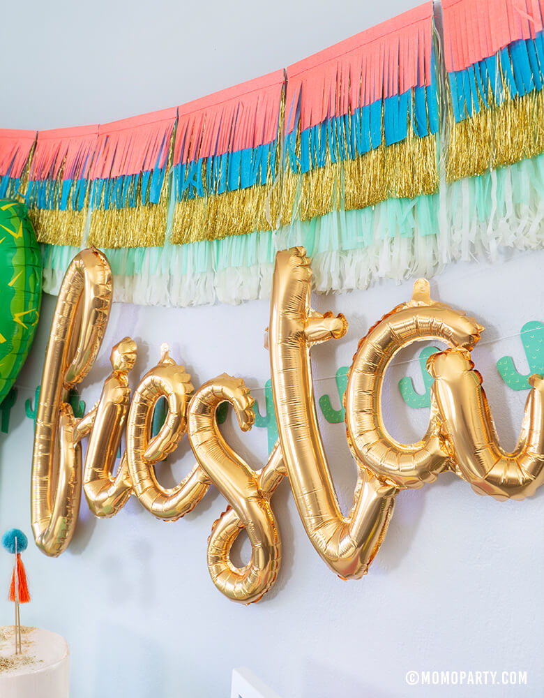 Fiesta Cactus Theme party backdrop inspiration with Meri Meri Colorful Fringe Large Garland, Fiesta Gold Script Mylar Balloon, My Mind's Eye's Cactus Banner