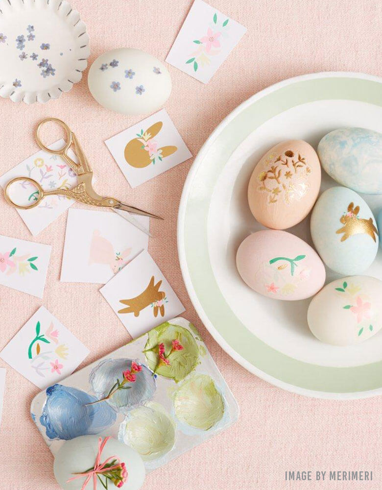 A table with pastel Easter eggs decorated with Meri Meri's Floral Bunny Egg Decoratung Tattoo Kit for kids Easter celebrations