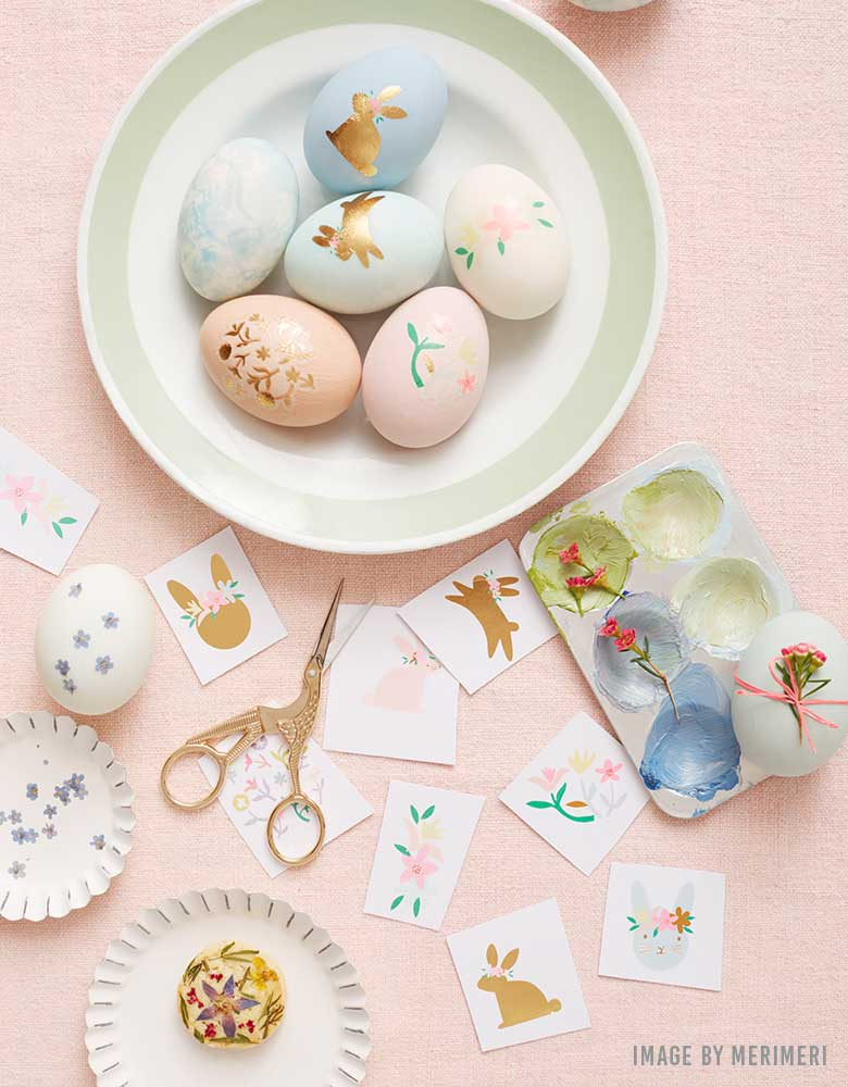 An Easter craft table with pastel Easter eggs decorated with Meri Meri's Floral Bunny Egg Decoratung Tattoo Kit for kids Easter celebrations