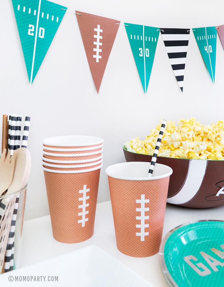 kid football themed birthday party with classic football printed design paper cups, Football Tailgate banner, popcorn in a bowl,  great for a football viewing, Super Bowl or tailgate party!