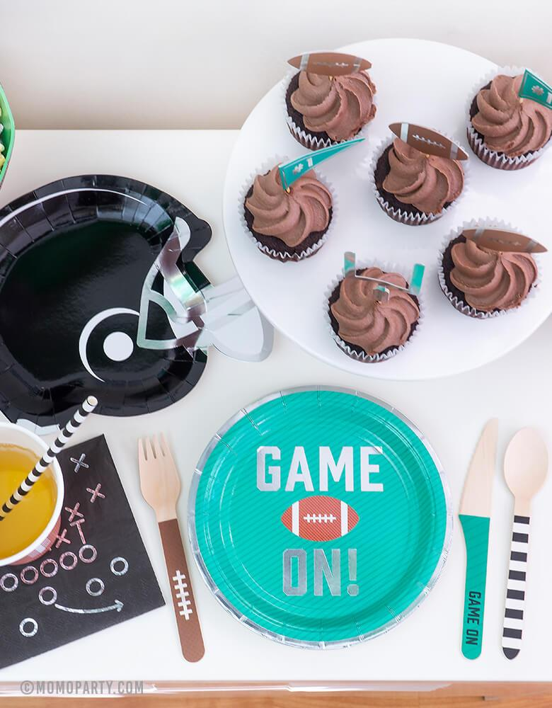 Football Party set up idea with Green Game on Football Party Paper Plates, Black Game Play Napkins, Football Tailgate Helmet Appetizer Plates, chocolate Cupcake with Tailgate Treat Picks, Football Tailgate Wooden Cutlery Set, simple modern party ware for kid football themed birthday party or super bowl celebration