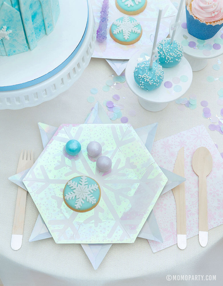 Frozen Inspired party supplies of Snowflake-designed plates, napkins, silver utensils on a whimsical table of party treats for a kids birthday party