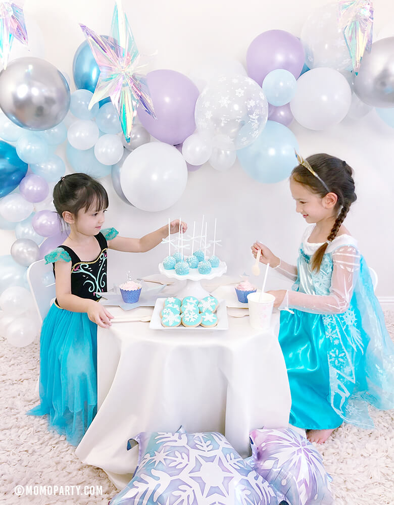2 girls wearing Disney frozen frozen princess elsa and anna's costumes, sitting on the desert table, with a beautiful balloon garland with Pearl purple, Chrome blue, pearl white, pearl blue, clear snowflake latex balloons, iridescent hanging starts back drop,  celebrating a Girl's Frozen birthday party