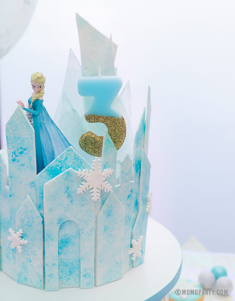 a Close up look of a Frozen Themed icy castle cake with Elsa Princess figure toy as a cake topper,  Talking Tables - We Heart Birthday Glitter Number 3 Candle in Blue and gold glitter, for a 3 years girl's disney frozen themed birthday party