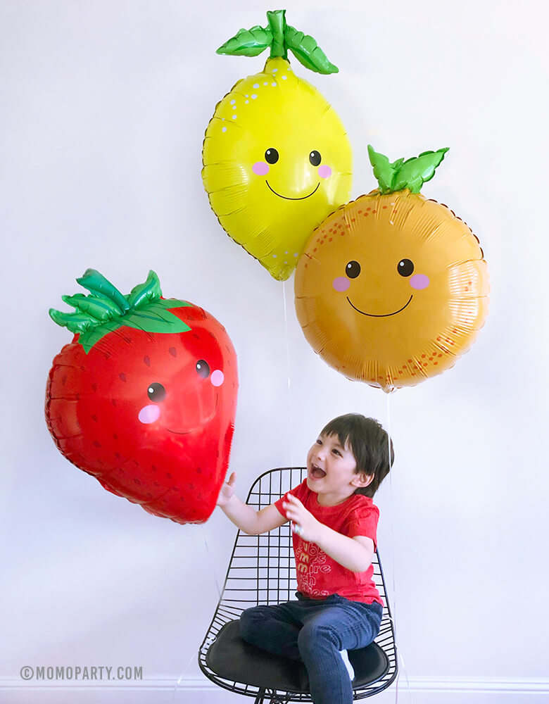 "a happy boy catching 3 Betallic Produce Pal 29"" Lemon, Strawberry and Orange Foil Mylar Balloons by sitting on a black Eames Wire Chair"