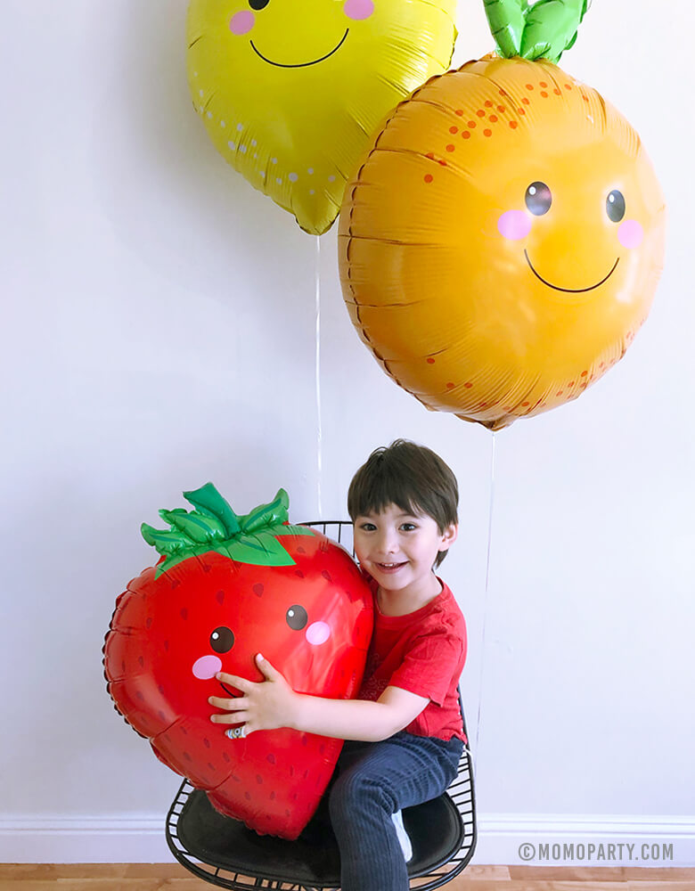 boy sitting under lemon and orange foil balloons and hugging Strawberry Foil Mylar Balloon