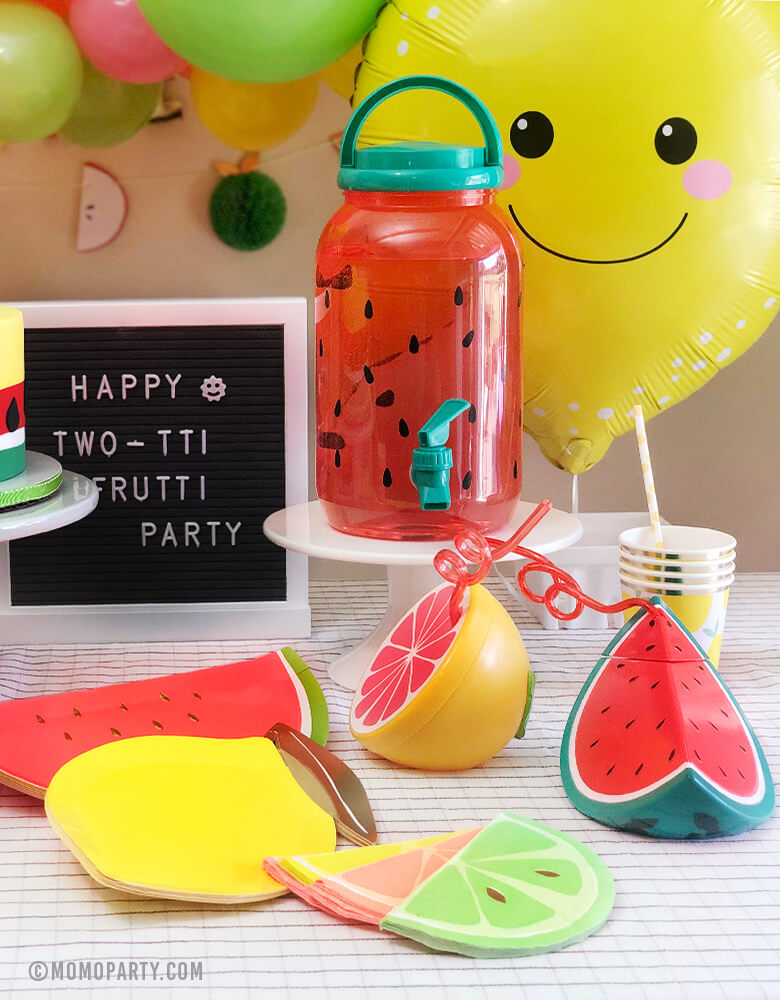 "Summer Bright Fruit themed party table decoration with watermelon and lemon paper plates, pink and mint circus napkins, Lemon paper cup, Sunnylife citrus and watermelon sippers, and big lemon Foil Balloon and letter board with ""happy two-tai Fruity Party"" sign"