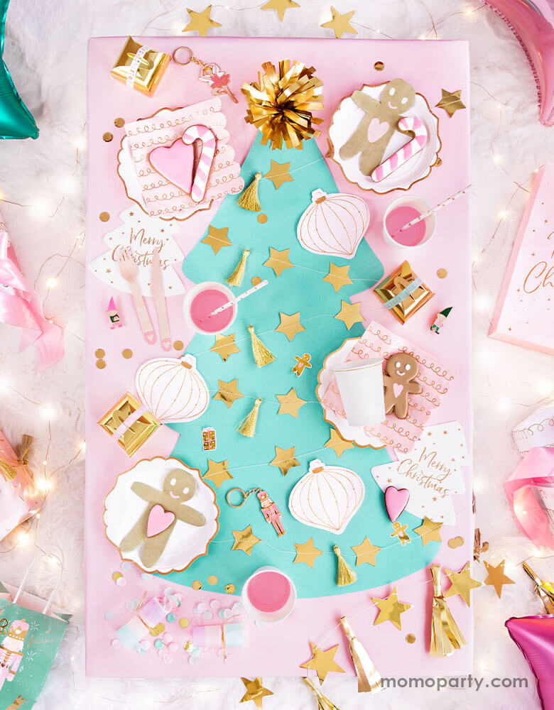 An adorable pastel Christmas themed party table filled with Party Deco's pink Christmas tableware including gingerbread man napkins, Christmas ornament napkins, pastel colored confetti and gold star banners  on a mint Christmas tree shaped table runner