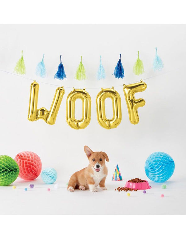 "A corgi dog in a dog-themed party with Northstar 16"" Woof Gold Mylar Balloons spelled out in the backdrop along with festive tassels and decorations"