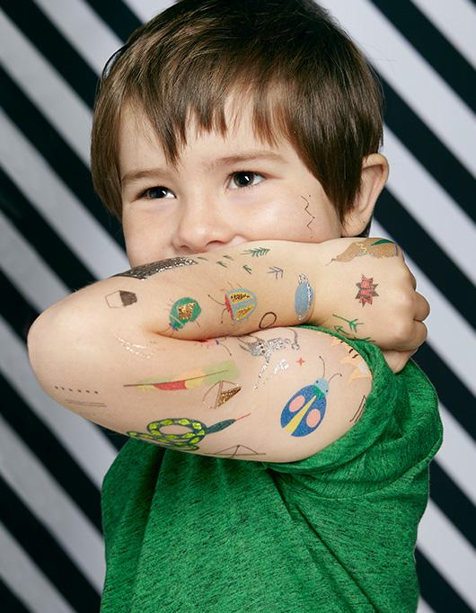 boy showing lots of cool Temporary Tattoos on his arm