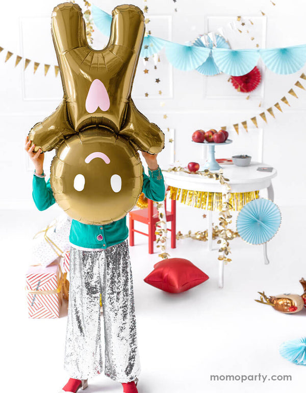 "A little girl in festive Christmas themed outfits holding Party deco's 34"" Gingerbread Man Foil Balloon upside down with Christmas decorations in the background"