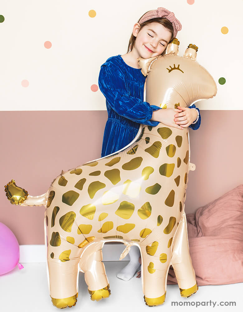 a girl with blue dress hugging a 40 inch Giant Smelling Giraffe Foil Mylar Balloon by Party Deco . This adorable giraffe shape foil mylar balloon in cream color with gold metallic prints is perfect for your little one's safari or zoo themed celebration, Nursery room decor, animal party, baby shower ect