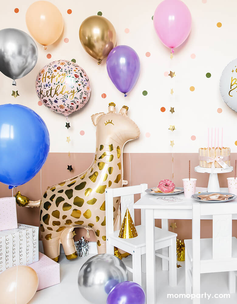 A loving birthday celebration at home, fill with lots of gold, pink, blue, silver, blush latex balloons, Junior Floral Happy Birthday Foil Balloon, Gifts on the conner of the room next to a 40 inch Giant Smelling Giraffe Foil Mylar Balloon by Party Deco standing next to the kids desk and chairs. there are cake, donut, sweets, and party ware on the kid's table. Ready for the little one's safari or zoo themed birthday celebration