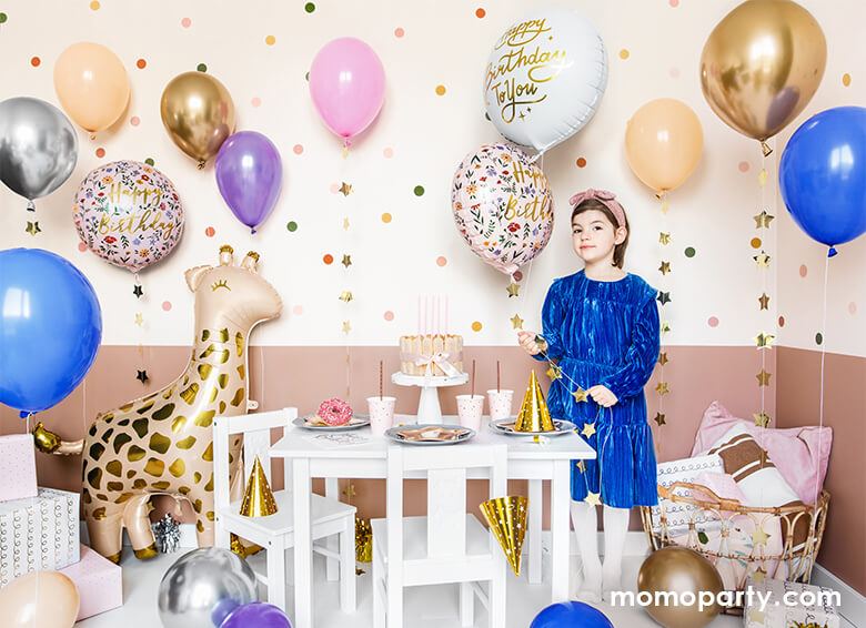 A loving birthday celebration at home, fill with lots of gold, pink, blue, silver, blush latex balloons, a girl wearing a blue dress holding a Junior Floral Happy Birthday Foil Balloon, Gifts on the conner of the room next to a 40 inch Giant Smelling Giraffe Foil Mylar Balloon by Party Deco standing next to the kids desk and chairs. there are cake, donut, sweets, and gold party hats, and party ware on the kid's table. Ready for the little one's safari or zoo themed birthday celebration
