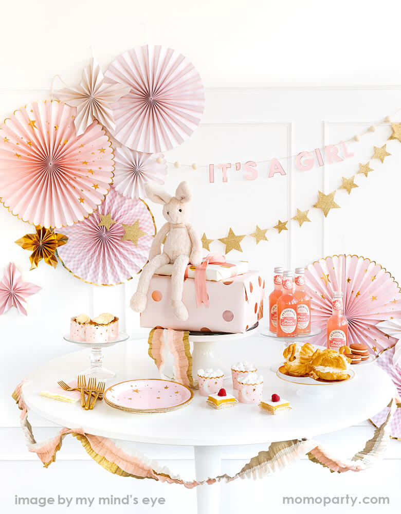 A Baby Girl Shower Table decorated with My Mind's Eye baby collection in baby pink and star designs, cute pink bunny toy sitting on a pink gold polka dot wrapped gift box, sweets and drinks.  A beautiful Pink baby fan, It's a girl banner, gold star banner hanging at the back, Baby Pink/Cream/Gold Crepe Festoon dressing at the table's edge.